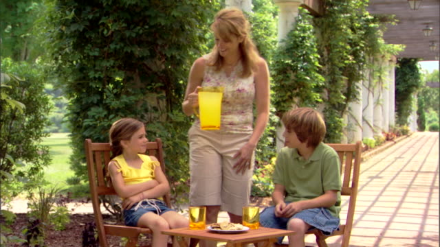 mom brings two children lemonade and pours it in their glasses. - 注ぎ口点の映像素材/bロール