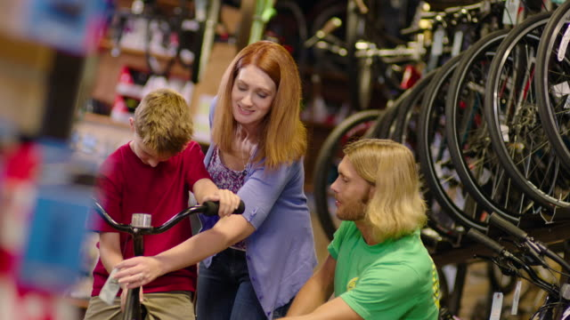 Mom checks price tag while excited boy inspects new bike with help from shop worker