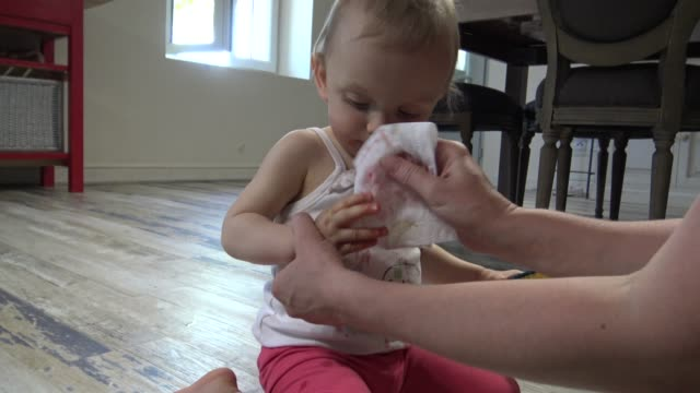 mom cleans baby's face in the kitchen - birichinata video stock e b–roll