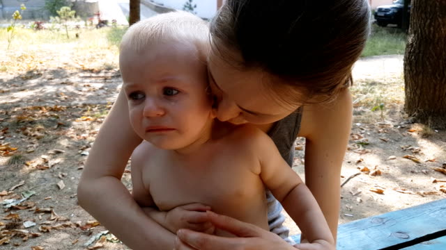 Mom consoling and breastfeeding her crying baby outdoors