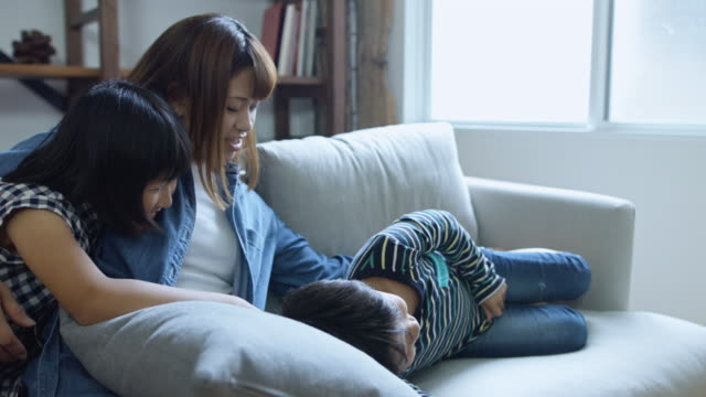 mom cuddling kids on couch - japanese mom stock videos & royalty-free footage