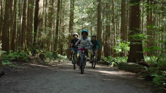 mom cycles on bike in forest with adolescent son and daughter - childhood stock videos & royalty-free footage