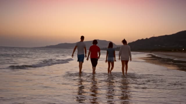 slo mo mom, dad and two teenage kids walking on the beach at sunset - family with two children stock videos & royalty-free footage