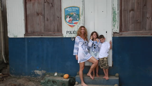 mom, daughter and son in matching outfits stand in front of spanish police station barefoot and boy tries to kiss sister and sister pushes him away as mom and daughter make dance moves and boy runs away. - matching outfits stock videos & royalty-free footage
