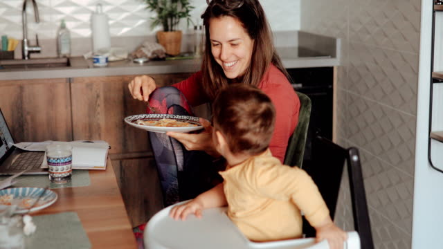 vidéos et rushes de maman mangeant son petit déjeuner et parlant à son fils d'enfant en bas âge - petit déjeuner