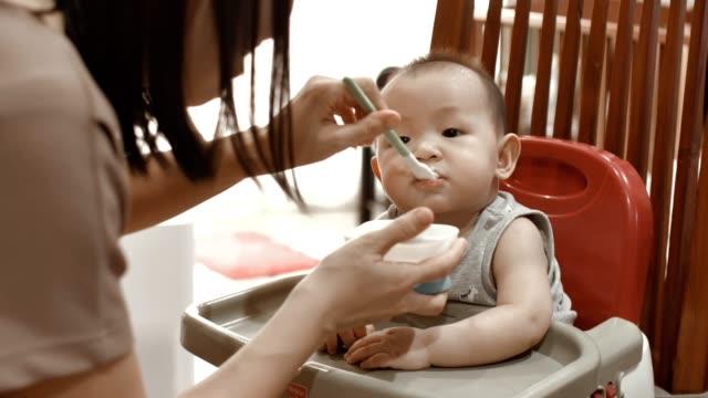 vídeos de stock, filmes e b-roll de mãe alimentando bebê filho (6-11 meses) - rotina