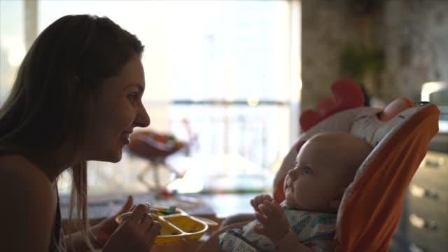 vídeos de stock, filmes e b-roll de mãe alimentando seu filho em casa - alimentando