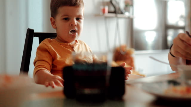 mom feeding her son while his watching cartoons on smartphone - yoghurt stock videos & royalty-free footage