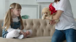 Mom gives daughter a puppy with a red bow