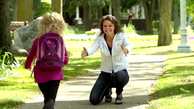 mom greets daughter coming home from school - primary age child stock videos and b-roll footage