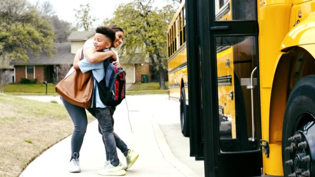 mom greets son after he gets off of school bus - getting out stock videos & royalty-free footage