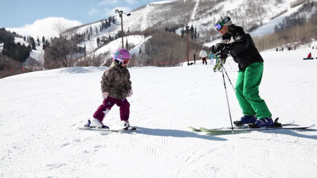 ms mom helping child ski while skiing with family / park city, utah, united states - park city utah video stock e b–roll