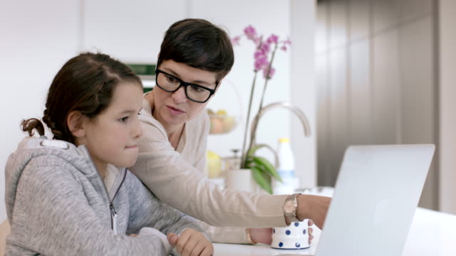 Mom helping daughter on laptop with homework