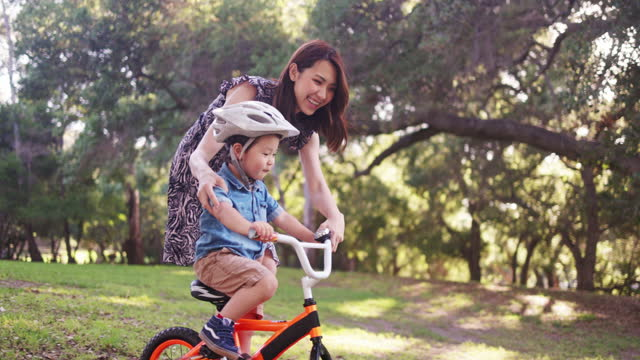 mom helping son riding a bicycle - riding stock videos & royalty-free footage