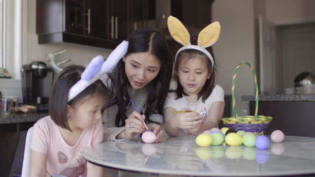 媽媽説明兩個年輕女孩的亞裔彩色復活節彩蛋 - 復活節 個影片檔及 b 捲影像