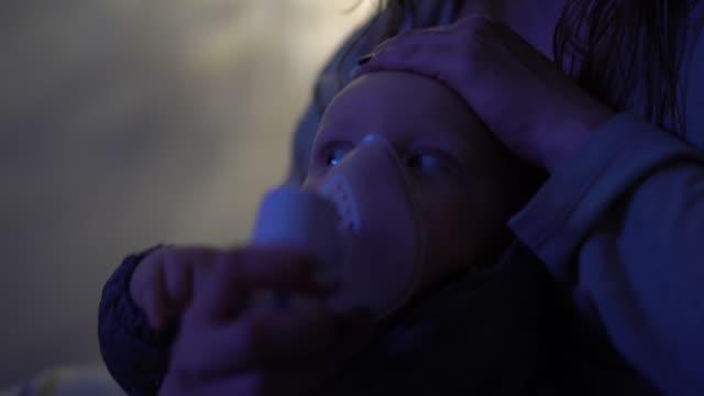 vídeos de stock, filmes e b-roll de mamã que prende um inalador da máscara do vapor para seu bebê - bronquite