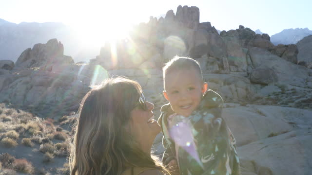 a mom holding and laughing with her toddler son while camping. - lens flare stock videos & royalty-free footage