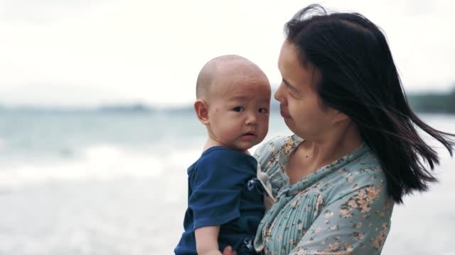 vídeos de stock e filmes b-roll de mom holding baby boy on beach - ecoturismo
