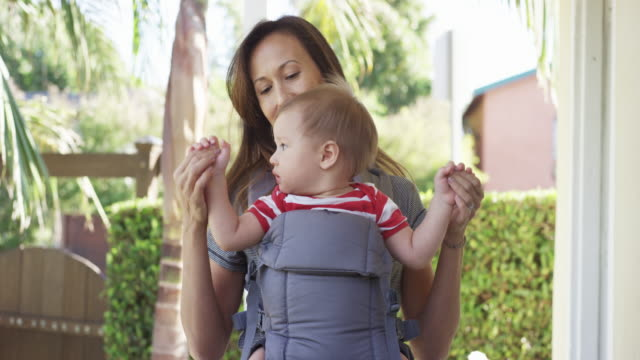 mom holding baby in baby carrier - baby carrier stock videos & royalty-free footage