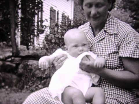 vidéos et rushes de 1936 mom holding baby in lap - bébés filles