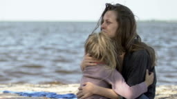 Mom hugging daughter and crying, sitting together on beach, survive in shipwreck