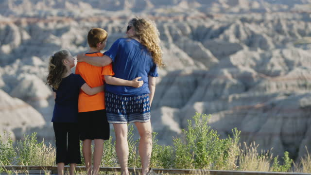mom hugs son and daughter at scenic overlook on family vacation to badlands national park. - badlands national park video stock e b–roll
