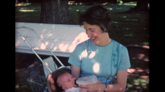 1961 mom in blue dress bottle feeding infant - powdered milk stock videos & royalty-free footage