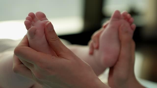 vidéos et rushes de maman donne à son bébé un massage des pieds. elle pétrit son pouce sur la plante de ses petits pieds. transmet l'amour le lien qu'une mère a à son bébé. - liens affectifs