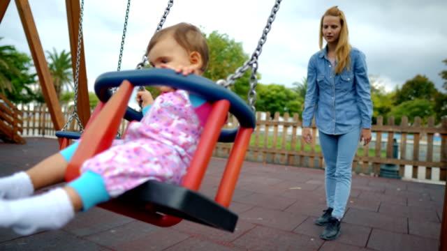 vídeos de stock e filmes b-roll de mom is playing with her little daughter on a swing outdoor - família jovem