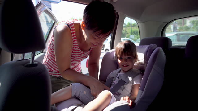 mom is putting cute little girl in to the safety seat on the back seat in the car - baby girls stock videos & royalty-free footage