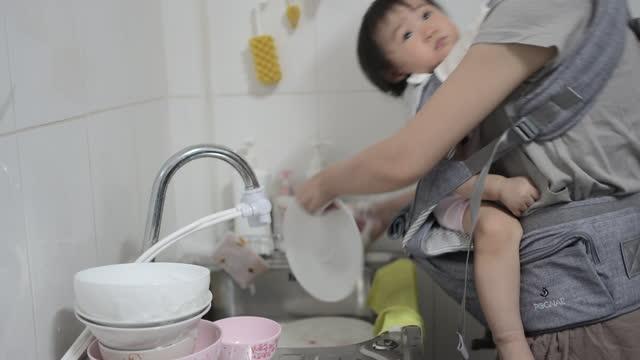 stockvideo's en b-roll-footage met mam wast de schotel in de keuken. - east asian ethnicity