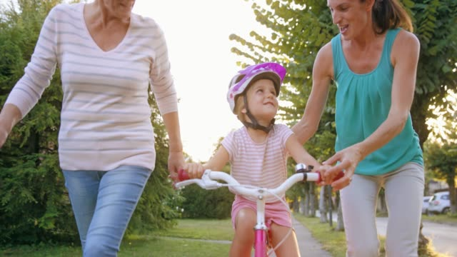 slo mo mom letting go of daughter's bike and the girl rides alone for the first time with the help of grandma running and cheering for her - vest stock videos & royalty-free footage