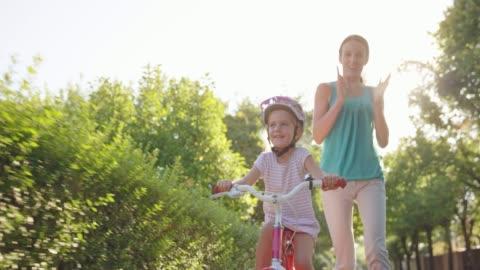 stockvideo's en b-roll-footage met slo mo moeder loslaten van de fiets haar jonge dochter is rijden voor de eerste keer op een zonnige straat - cycling