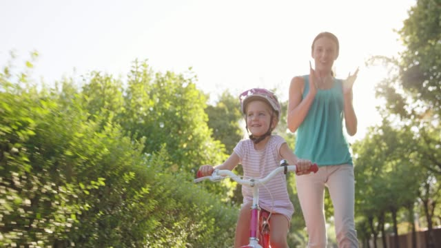 slo mo mom letting go of the bike her young daughter is riding for the first time on a sunny street - bicycle stock videos & royalty-free footage