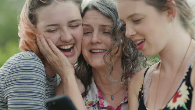 MS. Mom looks at smartphone with girls and kisses her daughter.