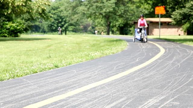 stockvideo's en b-roll-footage met mom on bike with trailer - aanhangwagen
