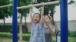 Mom playing with daughter on playground in park