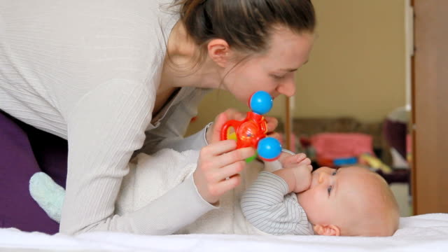 Mom plays with her baby with rattles