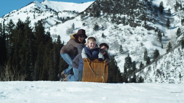 mom pushing her husband and son on a toboggan