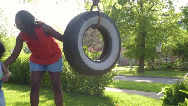 vídeos de stock, filmes e b-roll de mom pushing young son on tire swing - swing