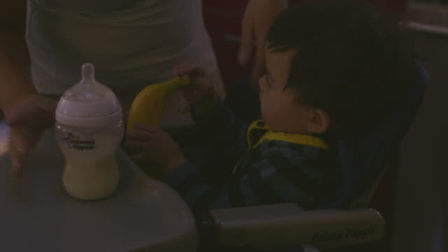 ms td tu mom putting him in chair with milk and banana / los angeles, california, united states - baby milk stock videos & royalty-free footage