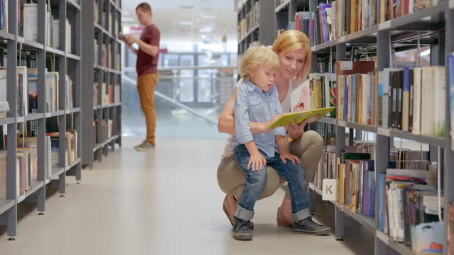 ds mom reading a book to her son in the library aisle - bookshelf stock videos & royalty-free footage