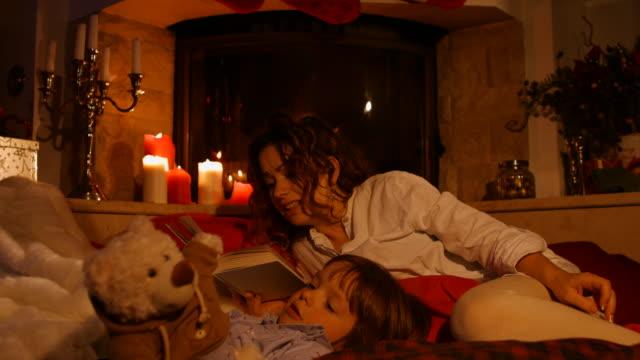Mère lire un livre à son fils avant l'heure du coucher