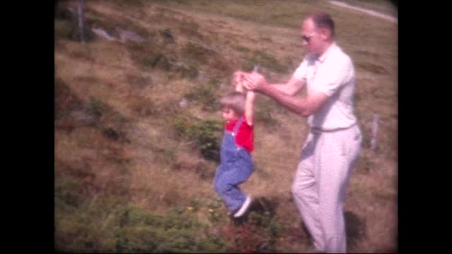 1963 mom removes bib from child, dad lifts her up mountain side