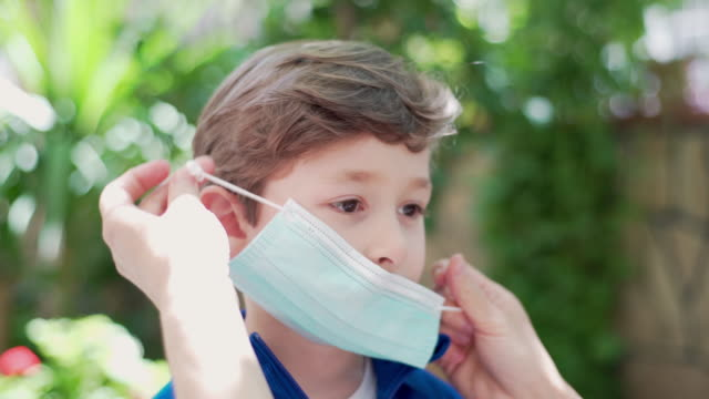 mom removing a surgical mask for her son - rimuovere video stock e b–roll