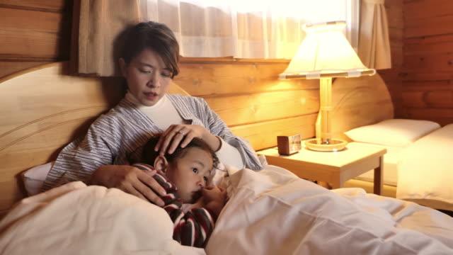 ママはベッドの上で眠りに落ちる彼女の赤ちゃんをこすった。 - 電灯点の映像素材/bロール