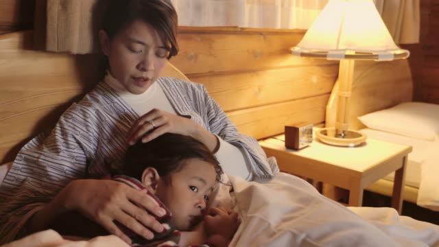 ママはベッドの上で眠りに落ちる彼女の赤ちゃんをこすった。 - 寝る前点の映像素材/bロール