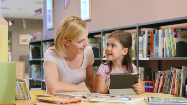 DS Mom supervising her daughter using a tablet in a public library