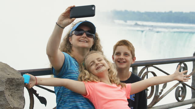MS. Mom takes smartphone selfies with smiling kids overlooking scenic Niagara Falls.