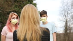 Mom Talking to Teenage Children With Face Masks on Outdoors